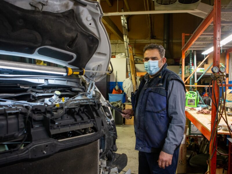 Owner at Icy Cool Automotive pictured with a mask and working on vehicle repairs.