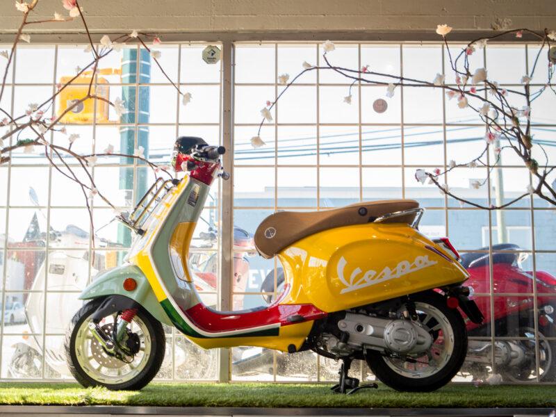 Brightly coloured Vespa Metro scooter pictured in a Spring window display.