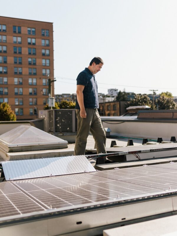 Owner at Eclipse Awards walking around the solar panels on their building's rooftop.