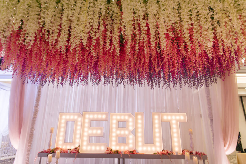 DEBUT Light up sign with a flower installation above.