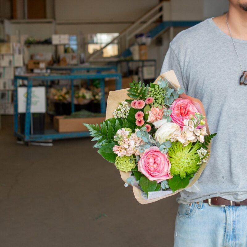 Staff member at Meyers Floral Company holding a bouquet of flowers.