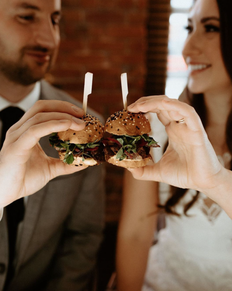 Couple enjoying sliders from Cocktails and Canapes.